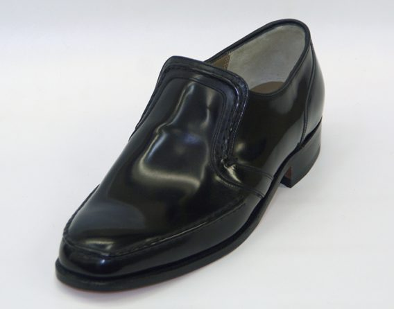 The Barker Shoes Hadley model from the Barker Heritage Collection is a black slip-on shoe with a hi-shine leather upper, and Goodyear welted sole with a leather stacked heel. Wide fitting.