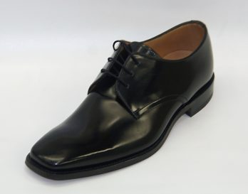 The 253B from Loake Shoes is a plain 3-tie derby lace up shoe, with a Hi-Shine Black Leather upper with Bicycle toe. It has leather Quarter lining with Leather Sock for added comfort. Full Leather Goodyear Welted Sole with Rubber Heel Top Pieces. The 253B is shown here in oblique view.